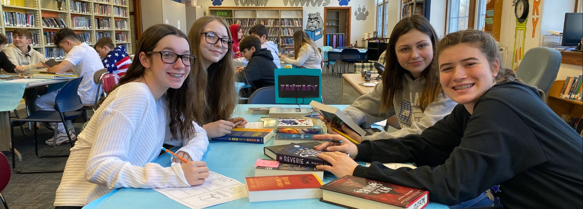 Eighth grade students in library looking at books as part of book tasting assignment.